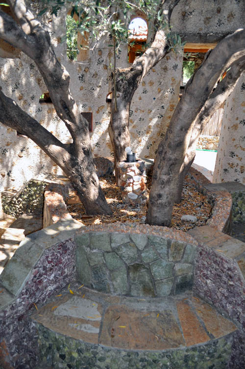 Mosaic stone benches around an olive tree inside a shady stone tower with an open roof